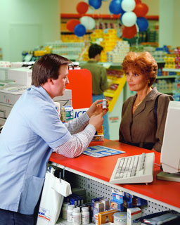 Phrmacist selling precription drugs to a customer at our pharmacy
